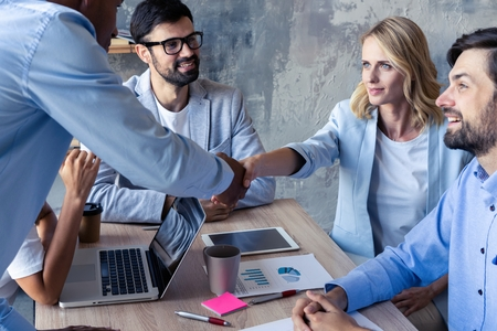 New business partners. Young modern colleagues in smart casual wear shaking hands and smiling while sitting in the creative office. Stock Photo