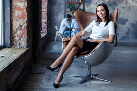 fashionable model sitting in a chair in office. Business, elegant businesswoman. 版權商用圖片