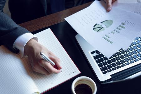 Geschäftsmann, der Investitionsdiagramme analysiert. Buchhaltung. Hände des Finanzmanagers, der während der Arbeit Notizen macht. Standard-Bild