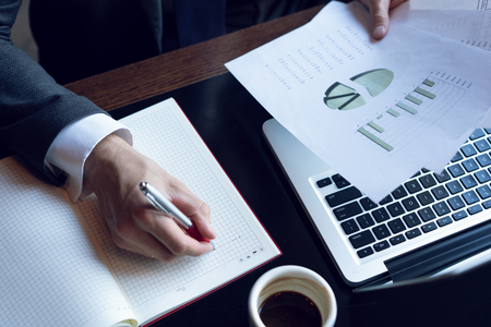 Uomo d'affari che analizza i grafici di investimento. Contabilità. Mani del manager finanziario che prendono appunti durante il lavoro. Archivio Fotografico
