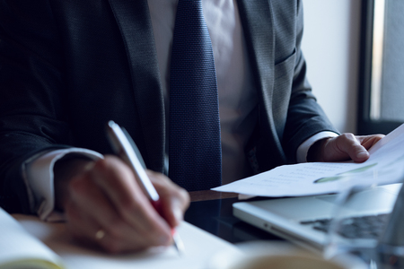 Homme d'affaires analysant les graphiques d'investissement. Comptabilité. Mains du directeur financier prenant des notes tout en travaillant.