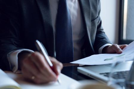 Zakenman die investeringsgrafieken analyseert. Boekhouding. Handen van financieel manager die aantekeningen maakt tijdens het werken.