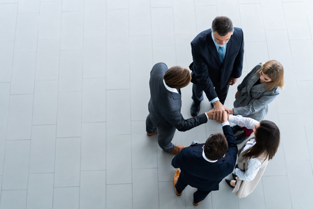 High angle view of a team of united coworkers standing with their hands together in a huddle in the modern office building.