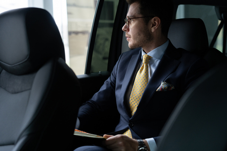 Young businessman sitting on back seat of the car, while his chauffeur is driving automobile. Stockfoto