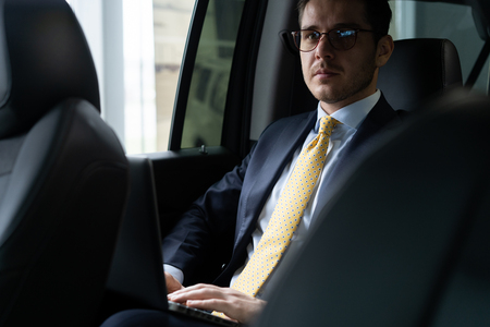 Young businessman sitting on back seat of the car, while his chauffeur is driving automobile. Stock Photo