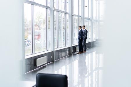 Two Businessmen Having Informal Meeting In Office Corridor. Stock Photo