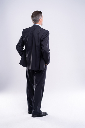 Businessman standing back to camera hands on hips on white background.