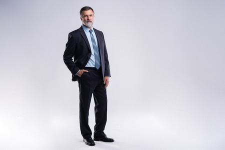 Full length portrait of confident mature businessman in formals standing isolated over white background. Stockfoto