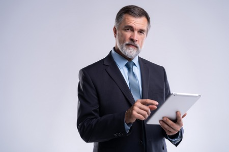Portrait of aged businessman wearing suit and tie. Businessman in years standing on white background. Boss using tablet computer. Imagens
