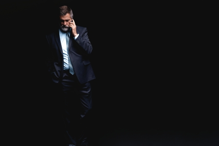 Portrait of a successful businessman on phone against black background.