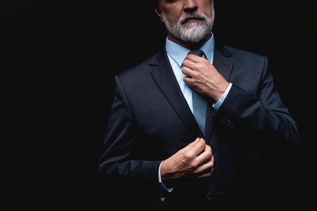 Man in a suit fixing his tie.