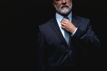 Man in a suit fixing his tie. Stock Photo