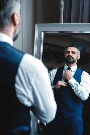 Elegant look. Full length of handsome man in full suit adjusting his jacket while standing in front of the mirror indoors. Archivio Fotografico