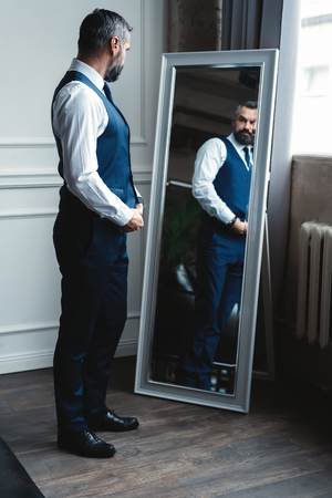 Elegant look. Full length of handsome man in full suit adjusting his jacket while standing in front of the mirror indoors. Banco de Imagens