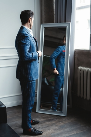 Perfect look. Reflection of handsome young man in full suit adjusting his jacket while standing in front of the mirror indoors. Imagens