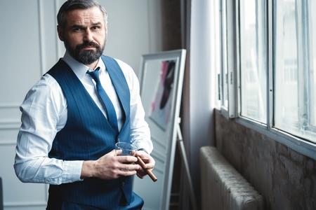 Uomo d'affari attraente con un sigaro e un bicchiere di whisky.