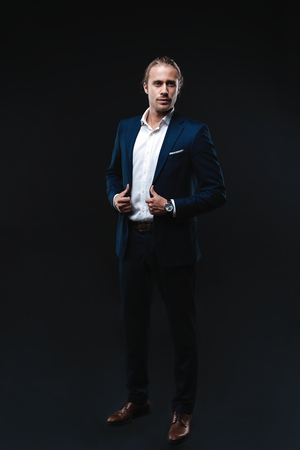 Full length of elegant young handsome man posing in fashionable suit, looking at camera. Studio shot