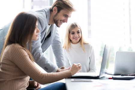 Sharing opinions. Group of young modern people in smart casual wear discussing business while working in the creative office.