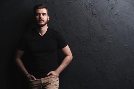 junger Modemann posiert für die Kamera auf schwarzem Hintergrund Standard-Bild