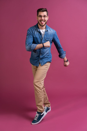 Funny man in casual is having some fun. He is posing and dancing. Isolated on pink background.