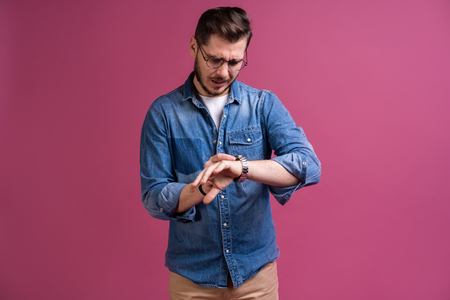 Portrait of a shocked man looking on wrist watch over pink background. Stock Photo