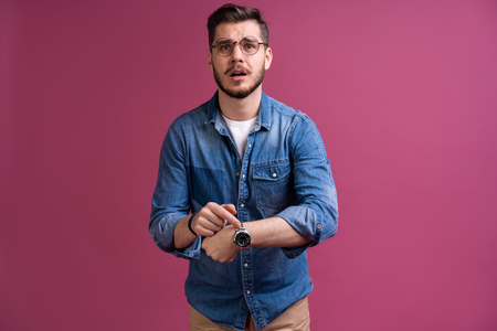 Portrait of a shocked man looking on wrist watch over pink background.
