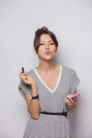 beautiful woman is applying her lips with pink lipstick,Woman with lipstick