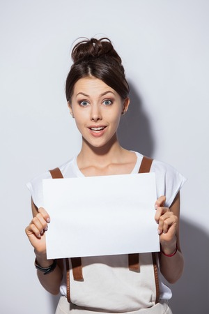 Smiling young pretty woman showing blank signboard, over white background isolated.