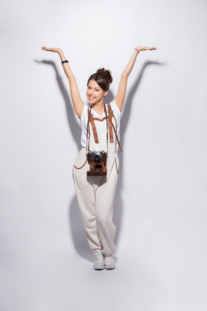 Full length portrait of a smiling casual woman standing on white background and looking at camera. Stock Photo