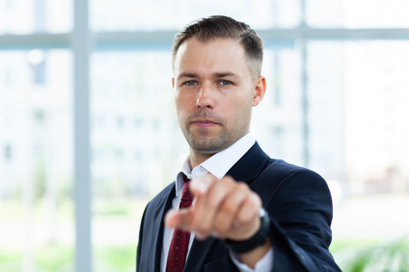 Handsome man pointing his finger at you on the background of business office. Stock Photo - 116123211
