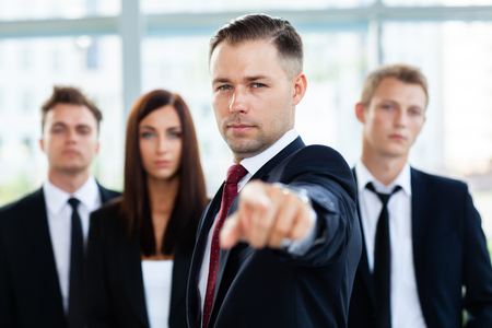 Handsome man pointing his finger at you on the background of business office.