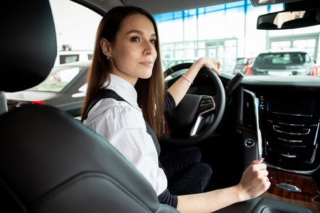 Young business woman test drive her new car.