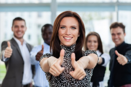 business concept - attractive businesswoman with team in office showing thumbs up. Imagens