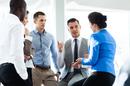 Image of business partners discussing documents and ideas at meeting. Stock Photo
