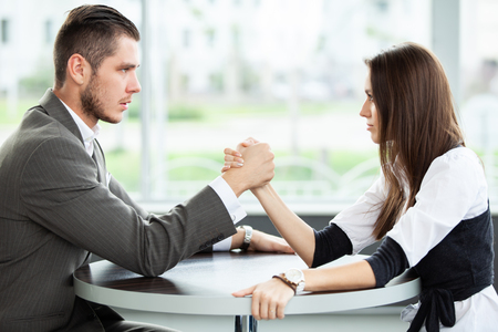 business and office concept - businesswoman and businessman arm wrestling during meeting in office. Stock Photo