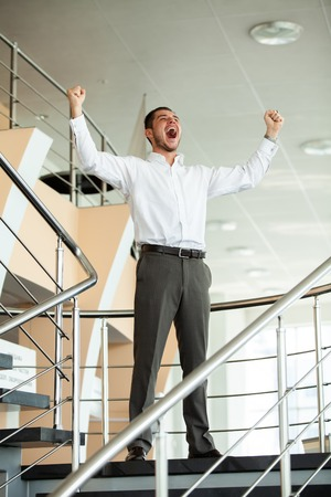 Celebrating success. Excited young businessman keeping arms raised and expressing positivity while standing in office building.