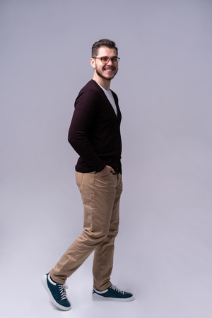 Full length portrait of a smiling young man walking isolated over gray background. Imagens