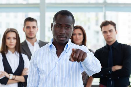 Gut aussehender Mann, der vor dem Hintergrund von Geschäftsleuten mit dem Finger auf Sie zeigt. Standard-Bild