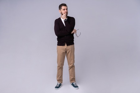 Young handsome man thinking over gray background. Banque d'images