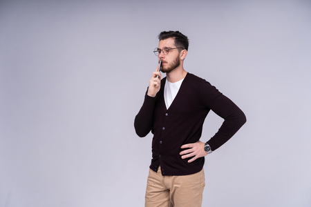 Young handsome man thinking over gray background. Stock Photo