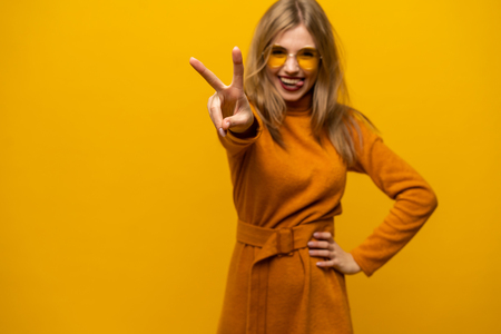 Image of happy young woman standing isolated over yellow background showing peace gesture. Looking camera Imagens