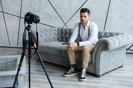 Young male blogger recording video at home.