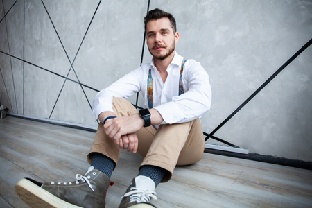 cool fashion male model sitting on grey background and looking at the camera. 스톡 콘텐츠 - 116156927