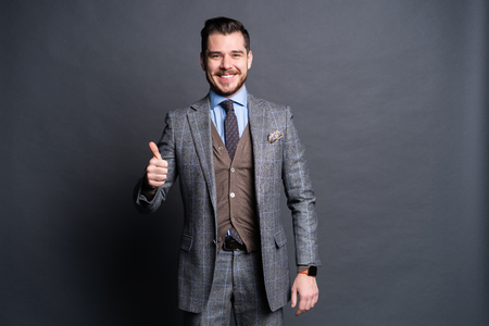 Portrait of excited satisfied cheerful confident positive handsome demonstrating thumbs-up pointing up isolated on gray background.