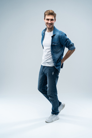 Modern and casual. Full length of handsome young man looking at camera with smile whilestanding against grey background.