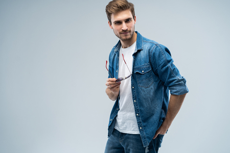 Portrait of stylish, stunning man in denim outfit standing over grey background.