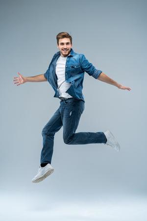 Ganzaufnahme eines glücklich aufgeregten bärtigen Mannes, der über grauem Hintergrund springt und die Kamera anschaut.