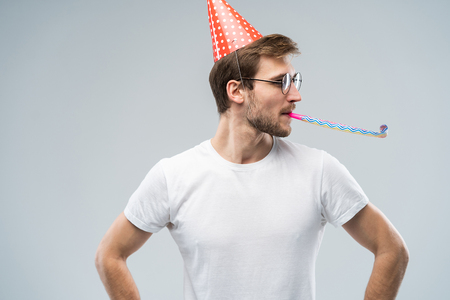 Studio shot of unshaven young Caucasian male blowing whistle while celebrating birthday, having relaxed and cheerful expression on his face Stock Photo