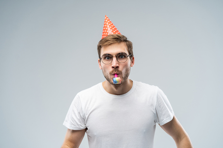 Studio shot of unshaven young Caucasian male blowing whistle while celebrating birthday, having relaxed and cheerful expression on his face Foto de archivo - 116347589