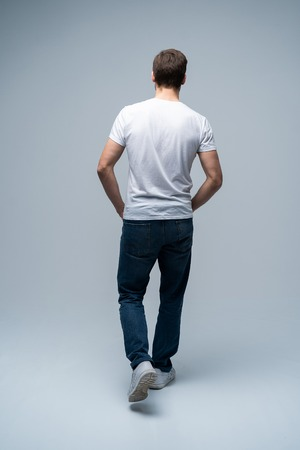 back view of a casual young man walking and looking to side on gray background. 免版税图像
